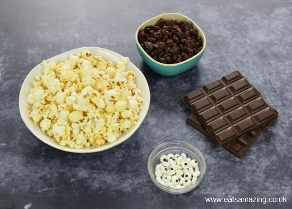 Ingredients for monster popcorn balls - popcorn, dark chocolate, raisins and candy eyeballs in bowls