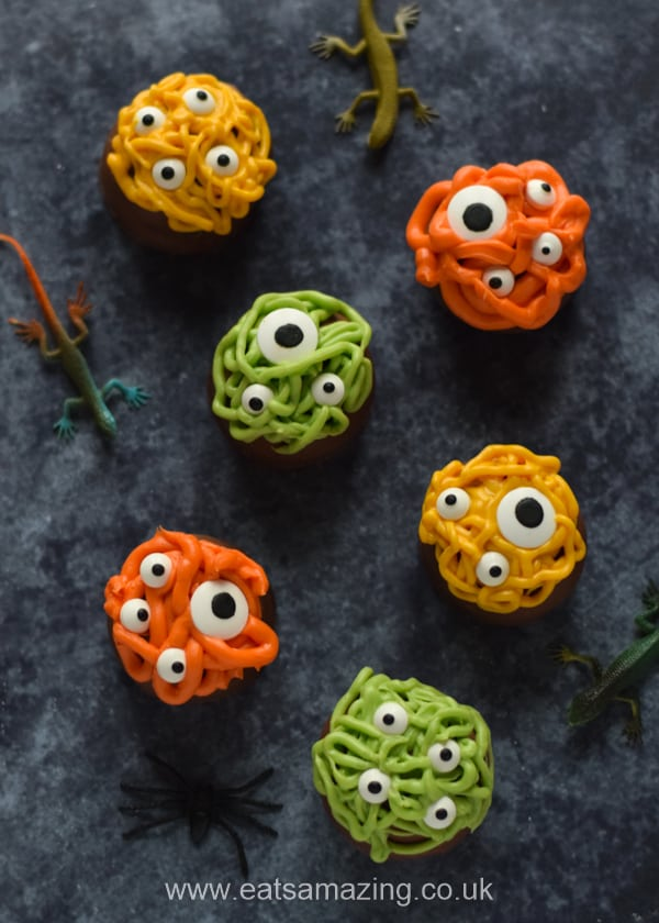 Monster teacakes for Halloween with toy lizards on a dark background