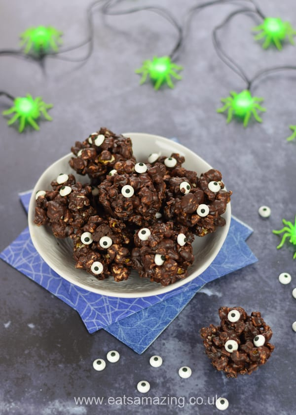 Bowl of Monster Dark Chocolate Popcorn Balls on a dark background styled for Halloween with spider napkins and spider fairy lights