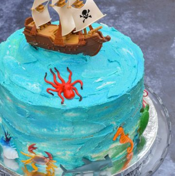 Blue ocean pirate themed cake with plastic animal and pirate ship decorations