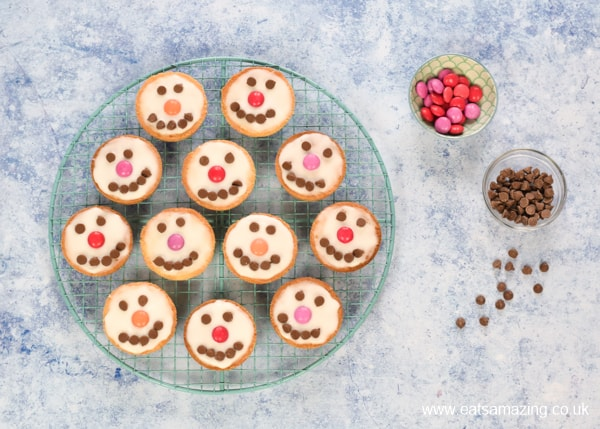 snowman shortbread cookies on a cooling rack with smarties and chocolate chips on the side