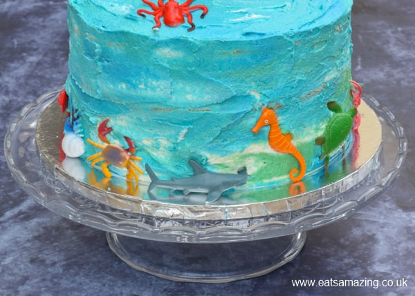 ocean themed cake viewed from the side - with watercolour buttercream icing decorated with ocean animal toys