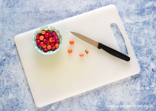 white chopping board with bowl of pink and orange smarties along with a sharp knife to demonstrate cutting smarties in half