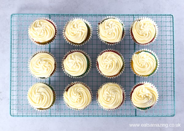 How to make easy rainbow cupcakes - step 5 pipe a swirl of buttercream on each cake