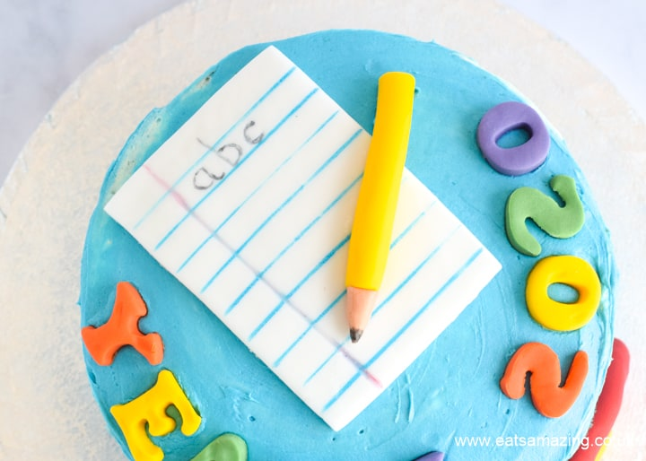 How to make pencil and paper cake decorations - step 3 draw on lines and letters then add to cake