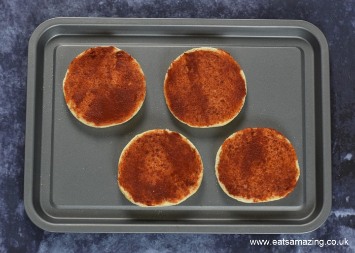 How to make Halloween Mummy Pizzas - step 2 spread a layer of tomato puree over each muffin