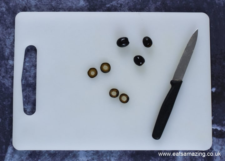 How to make Halloween Mummy Pizzas - step 5 cut black olives into rings