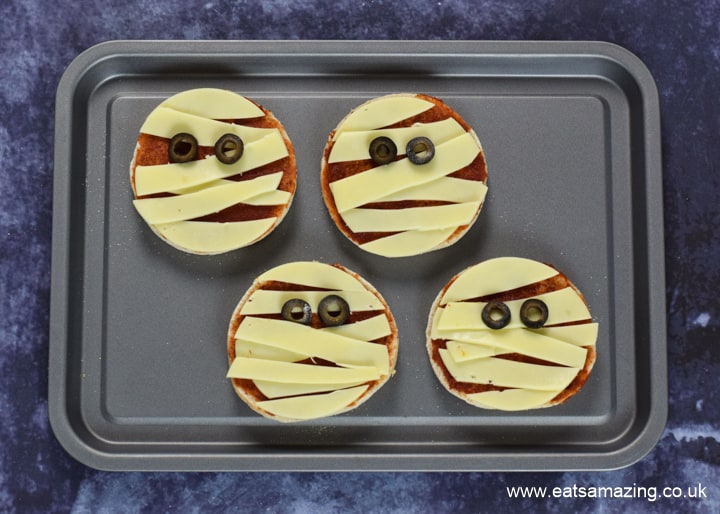 How to make Halloween Mummy Pizzas - step 6 add two olive eyes to each pizza