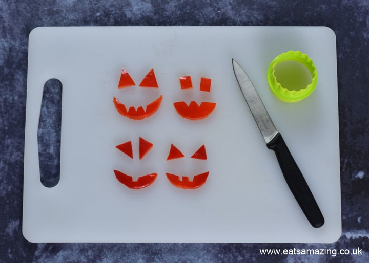 How to make Halloween Pumpkin Pizzas - step 5 cut pumpkin face shapes from red pepper
