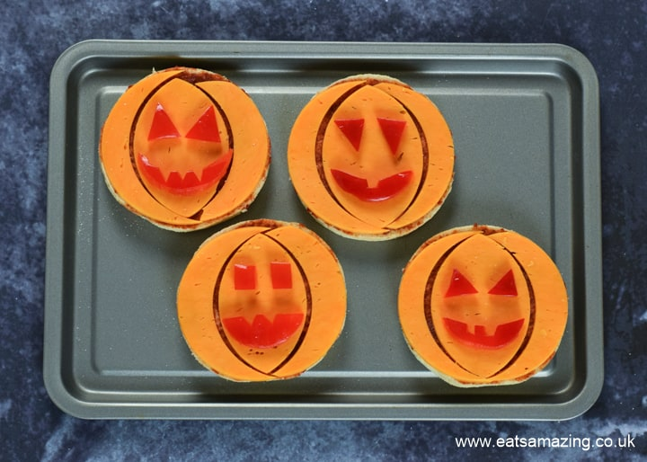 How to make Halloween Pumpkin Pizzas - step 6 arrange pepper faces on top of pizza