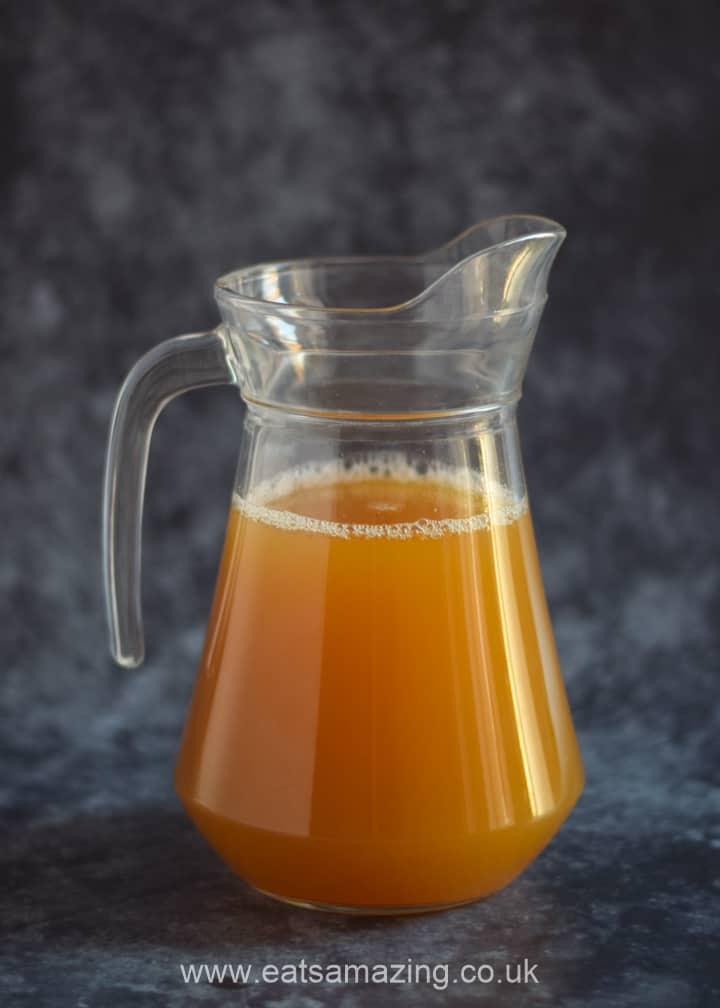 Worm juice recipe - fun Halloween mocktail for kids - step 2 add apple juice