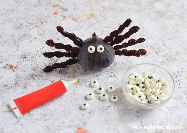 How to make fig and raisin spider snacks for Halloween - step 3 use writing icing to glue on edible candy eyes