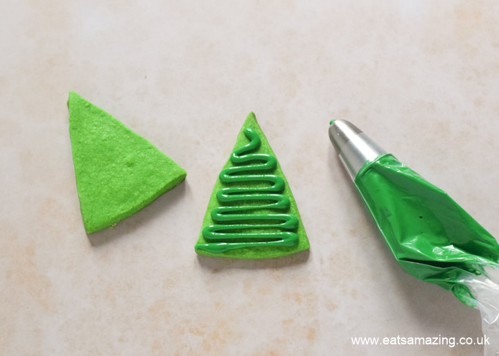 How to make easy Christmas tree cookies - step 3 pipe a zig zag of green icing over the triangle cookie