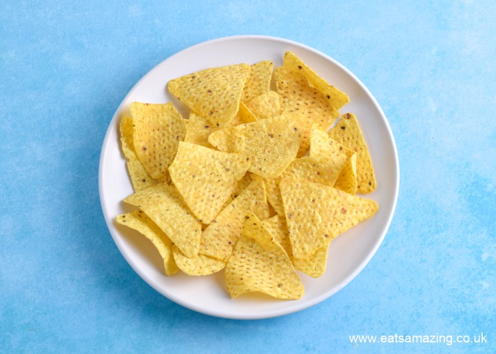 How to make nachos in the microwave - step 1 spread tortilla chips over a plate