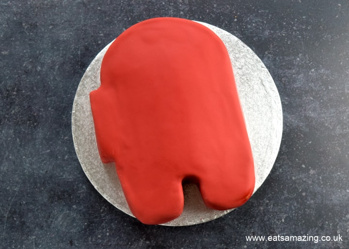 How to make an easy Among Us Crewmate Cake - step 6 cover cake with a sheet of red fondant
